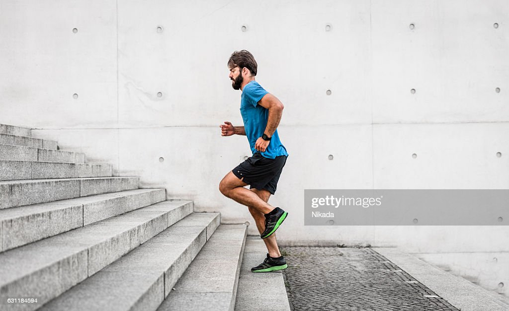 sporty man running up steps in urban setting : Foto stock