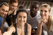Young smiling sporty multiracial friends taking group selfie photo holding looking at camera, happy healthy diverse fit people making self-portrait after working out together in gym, view from camera