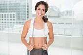 Sporty smiling brunette holding skipping rope in bright room