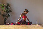 attractive athletic female stretching legs in sunny yoga studio