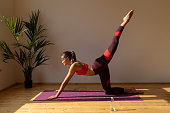 slim athletic woman doing stretching exercise in yoga studio, sunlight