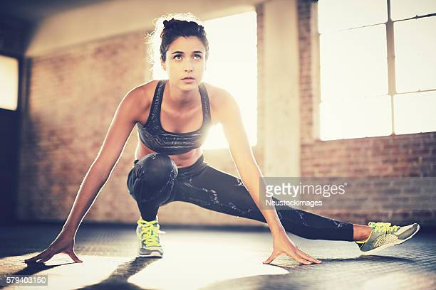 Sporty woman doing stretching exercise before workout in gym