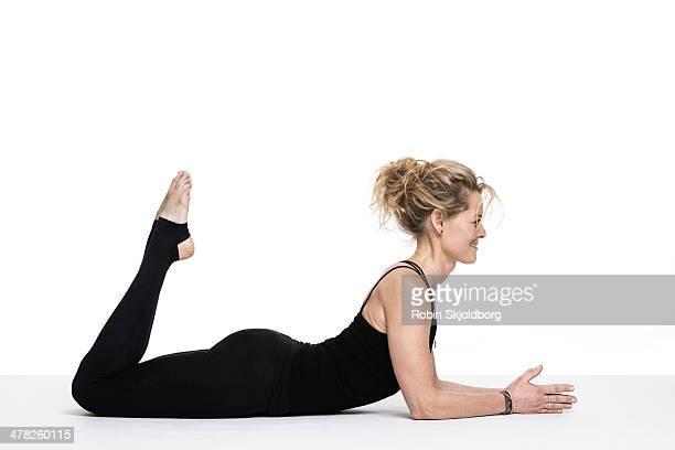 Sporty woman doing yoga exercises on floor