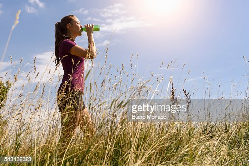 sporty woman drinking some water in nature