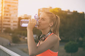 Beautiful sporty woman drinking water while resting from exercise.Image is intentionally toned.