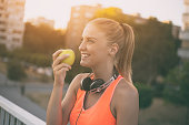 Beautiful sporty woman eating apple while resting from exercise.Image is intentionally toned.