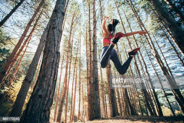 Sporty woman jumping in a forest