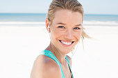 Portrait of young beautiful woman listening to music at beach. Close up face of smiling blonde woman with earphone looking at camera. Girl running at beach and listening to music.