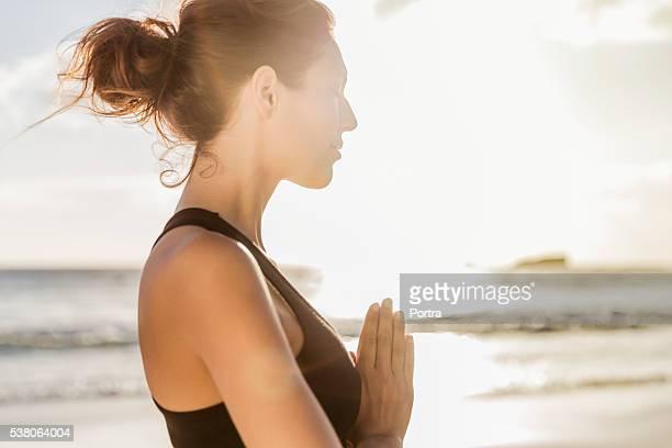 Sportliche Frau üben yoga am Strand