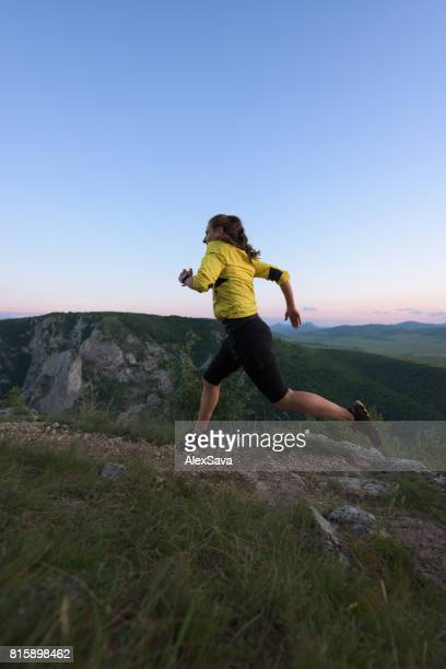 Sporty woman trail running in nature on a summer evening