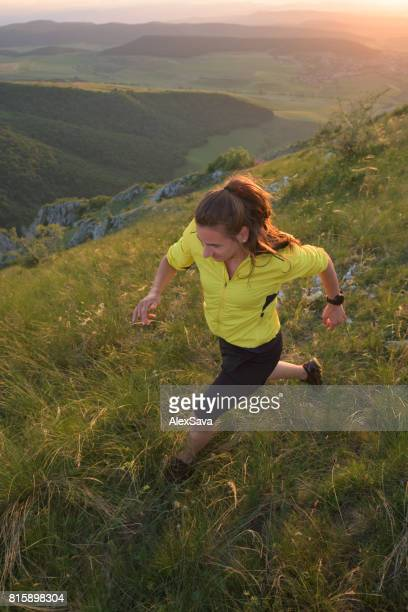 Sporty woman trail running outdoor in nature during sunset