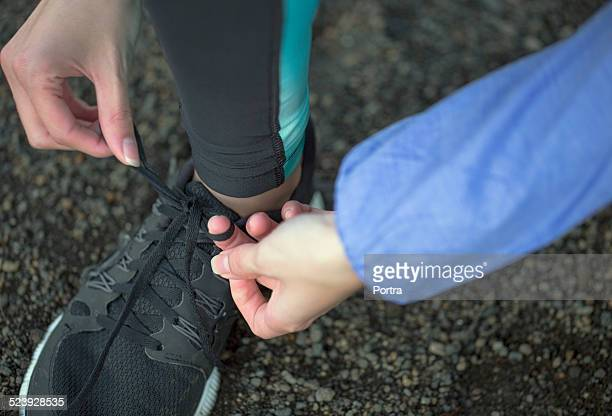 Sporty woman tying shoelace