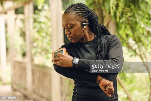 Sporty woman using mobile phone to monitor her fitness progress