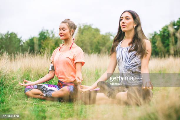 Sporty women doing yoga together