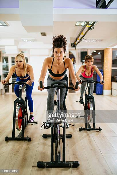 Sporty women spinning on exercise bike at modern gym.