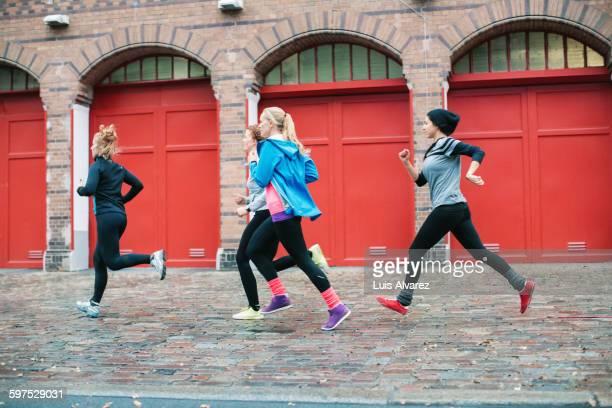 Sporty women jogging on sidewalk