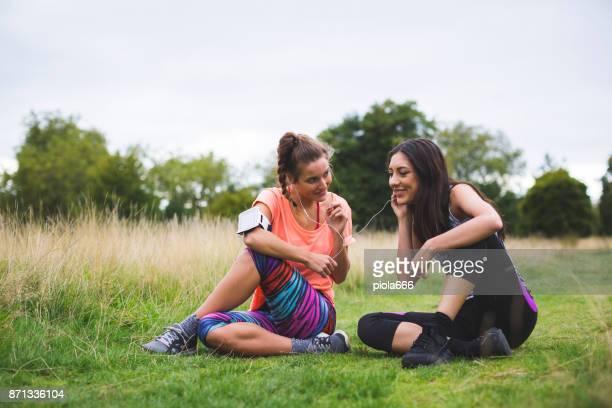 Sporty women sharing music after running