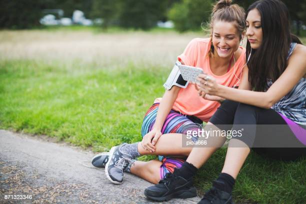 Sporty women sharing music on mobile after running