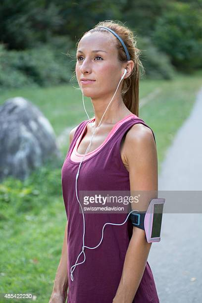 Sporty young woman listening music having break after running-outdoors.