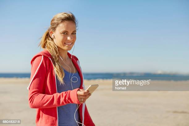 Sporty young woman listening to music at beach