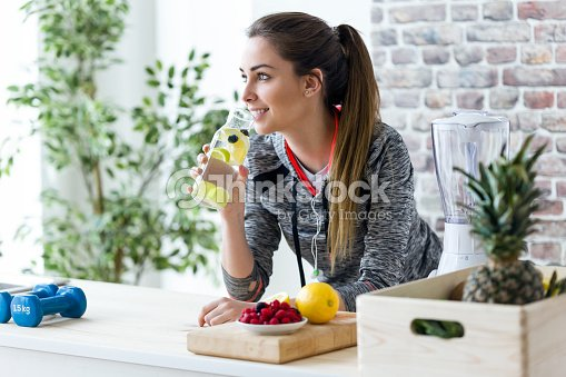 Sporty young woman looking sideways while drinking lemon juice in the kitchen at home. : Stock Photo