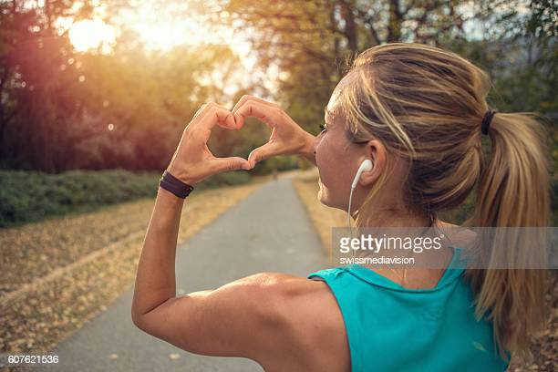 Sporty young woman makes heart shape finger frame at sunset