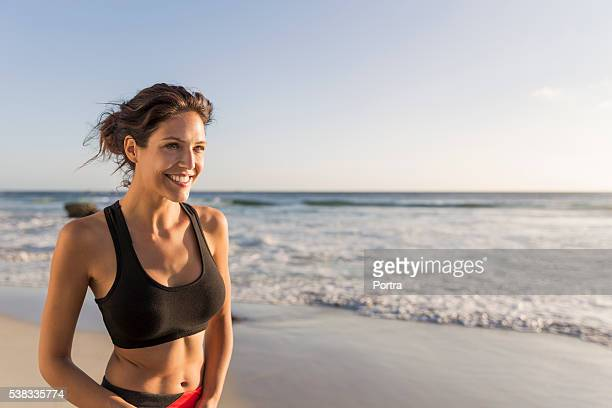 Sporty young woman smiling at beach