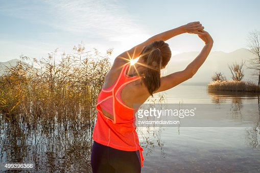 Sporty young woman stretching after jogging outdoors
