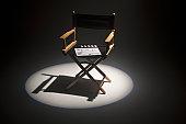 A spot lit directors chair and a clapper board