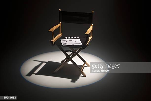 A spot lit directors chair and a clapper board
