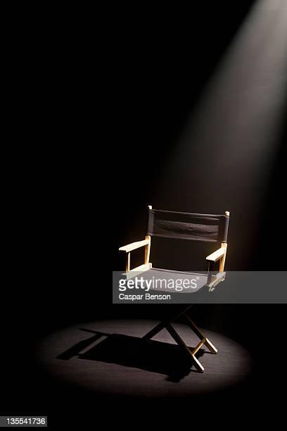 A spot lit directors chair