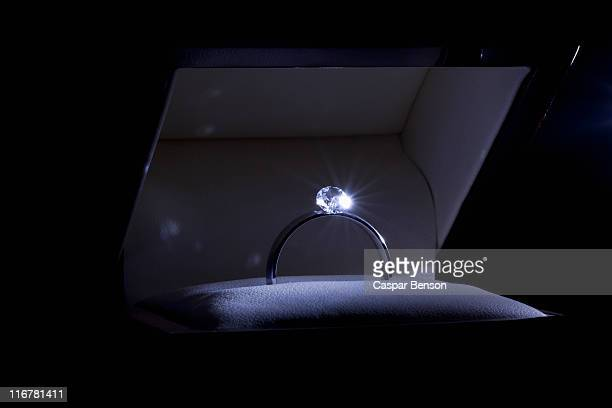 A spot lit engagement ring in a jewelry box, close-up