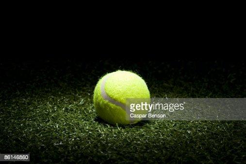 A spot lit tennis ball on turf