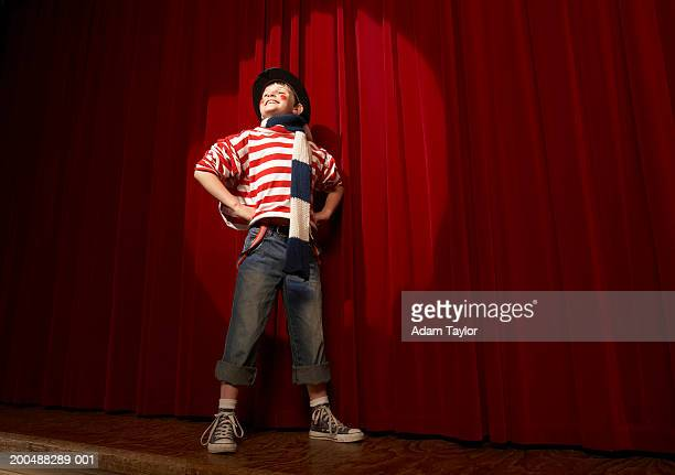 Spotlight on boy (8-10) in clown outfit, hands on hips, low angle view