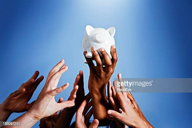 Enfoque en dinero: Muchas manos competir para mencionó piggybank