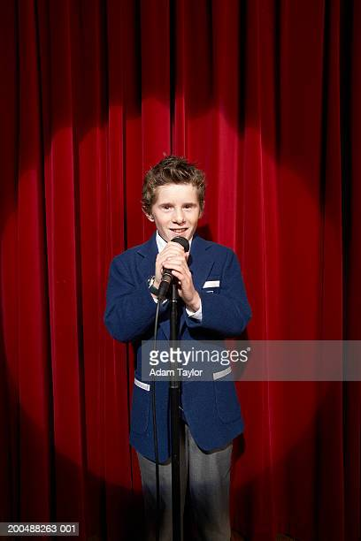 Spotlight on on boy (11-13) holding microphone on stage, portrait