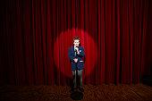 Spotlight on on boy (11-13) holding microphone on stage, portrait