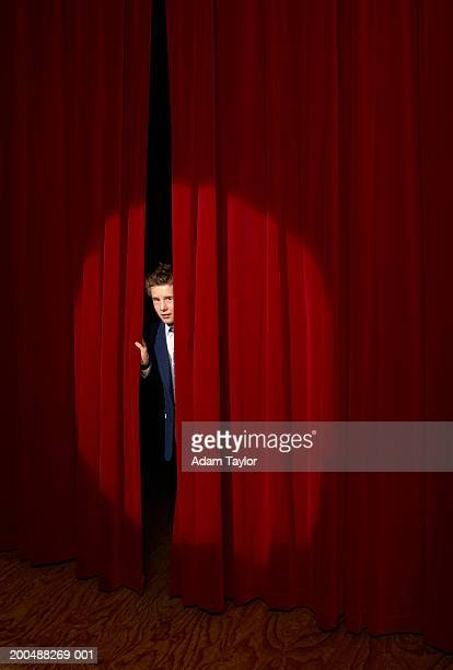 Spotlight on on boy (11-13) looking through curtains on stage