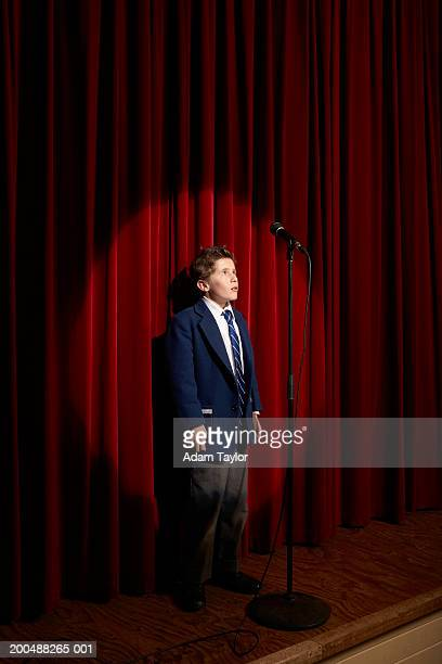Spotlight on on boy (11-13) standing behind microphone on stage