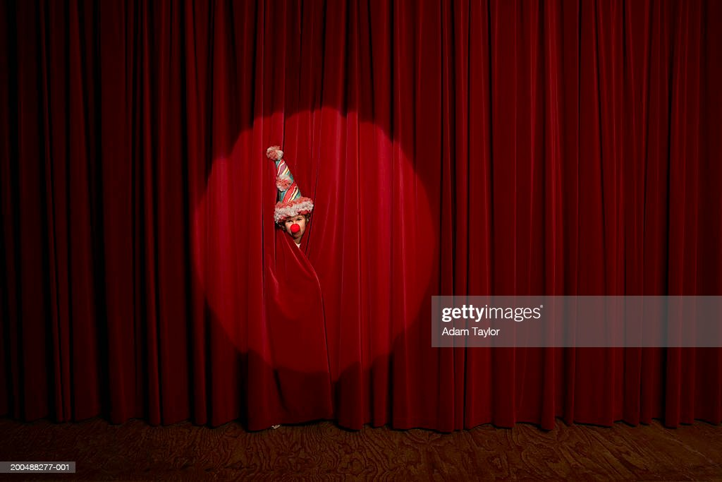 Spotlight on on boy (10-12) wearing clown hat peeking through curtains : Stock Photo