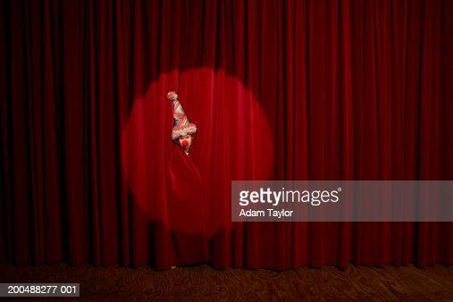Spotlight on on boy (10-12) wearing clown hat peeking through curtains : Stock Photo
