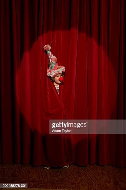 Spotlight on on boy (10-12) wearing clown hat peeking through curtains