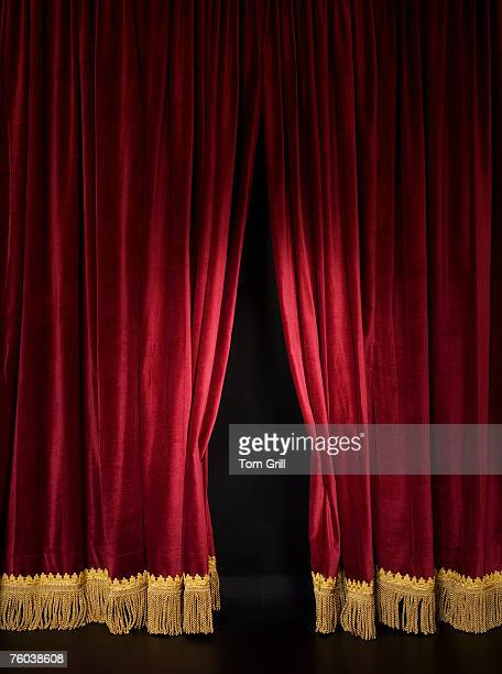 Spotlight on opening red stage curtain