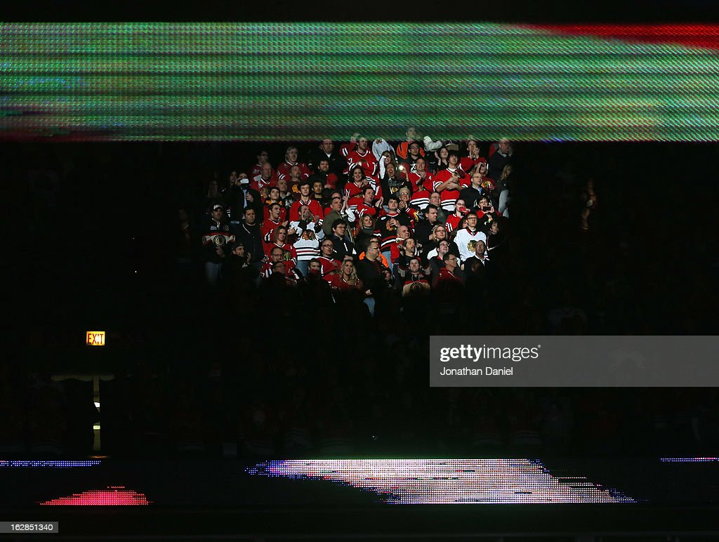 A spotlight signs on fans during the National Anthem before the Chicago Blackhawks take on the San Jose Sharks at the United Center on February 15, 2013 in Chicago, Illinois. The Blackhawks defeated the Sharks 4-1.