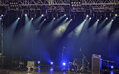 Spotlights and illumination on stage with drums, amplifiers, loudspeakers and other sound and music equipment