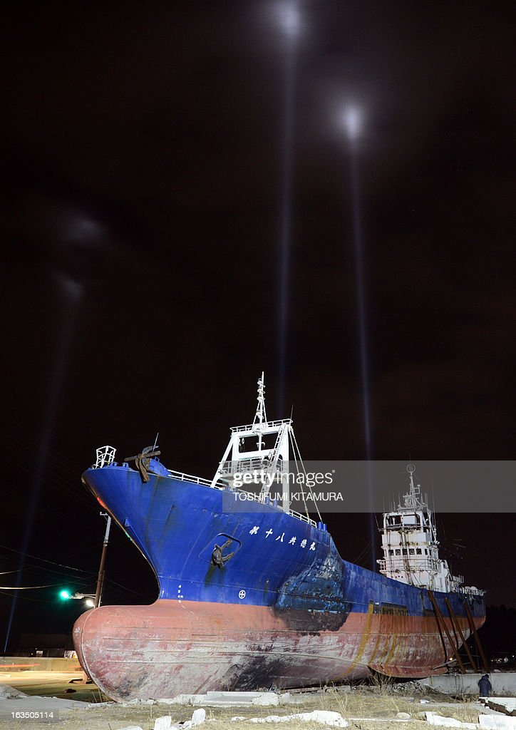 Spotlights are directed towards the sky as the No.18 Kyotoku Maru fishing boat (front) remains grounded, during a lightshow over Kesennuma city, Miyagi prefecture on March 11, 2013. March 11, 2013 marks the second anniversary of the 9.0 magnitude earthquake that sent a huge wall of water into the coast of the Tohoku region, splintering whole communities, ruining swathes of prime farmland and killing nearly 19,000 people. AFP PHOTO / TOSHIFUMI KITAMURA