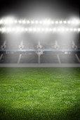 green soccer field empty with row of bright spotlights illuminating the stadium in night