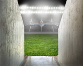 green soccer field empty with row of bright spotlights illuminating the stadium in night at arena tunnel