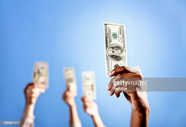 Spotlit hand holds up $100 bill with others in background