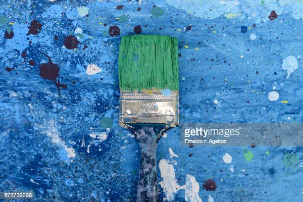 Spotted paintbrush over a painted surface